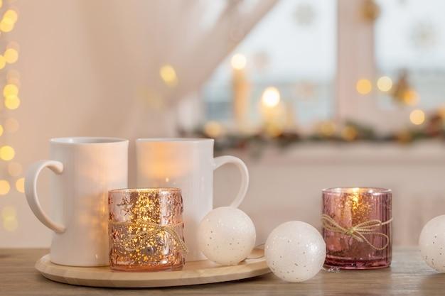 背景ウィンドウにクリスマスの装飾が施された2つの白いカップ