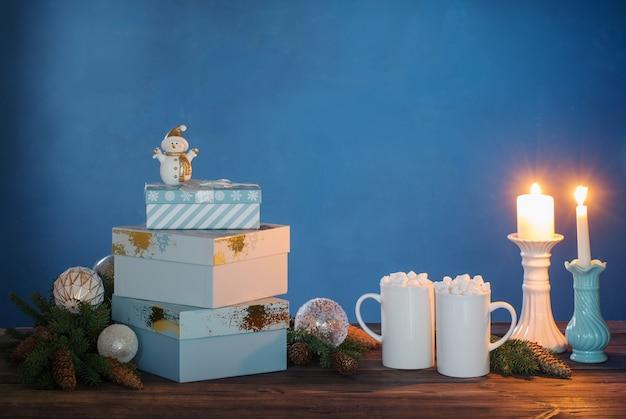 暗い背景にマシュマロとクリスマスの装飾と飲み物と2つの白いカップ