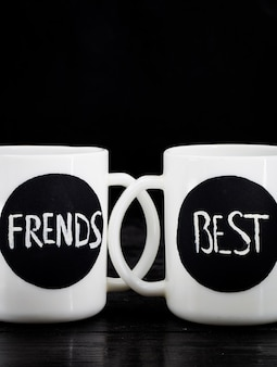Two white cups with the inscription standing on a black wood, holiday concept