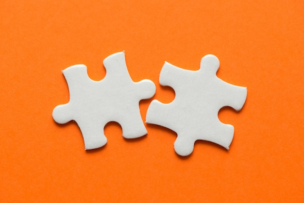 Two white details of puzzle on orange