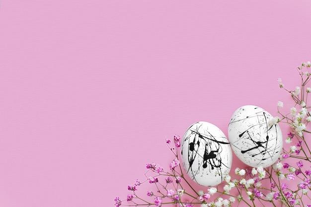 スペースのコピーとピンクの背景に黒い斑点と花の2つの白い卵。イースター。ミニマリズム。