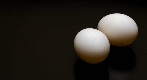 Два белых яйца на темном фоне с копией пространства