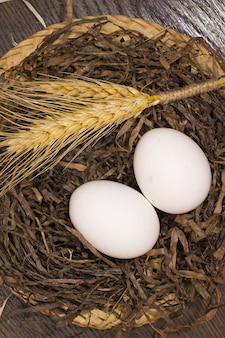 Two white eggs and wheat in the nest
