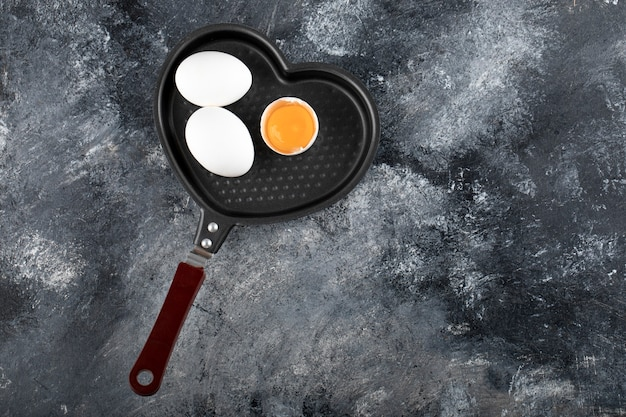 Two white eggs and yolk on heart shaped pan.