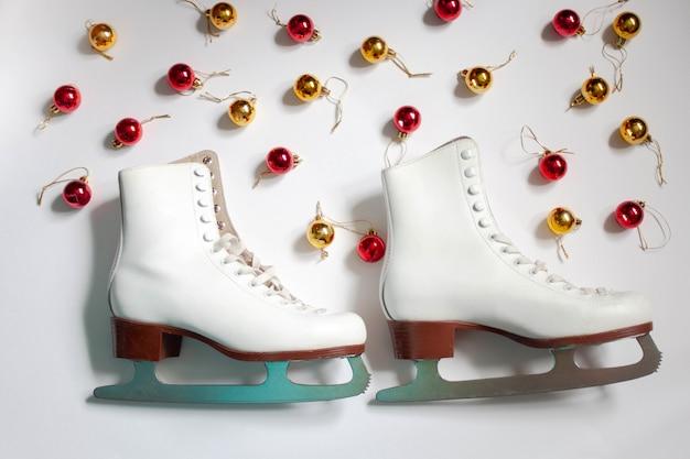 Two white figure skates on a white background around christmas balls are lying.
