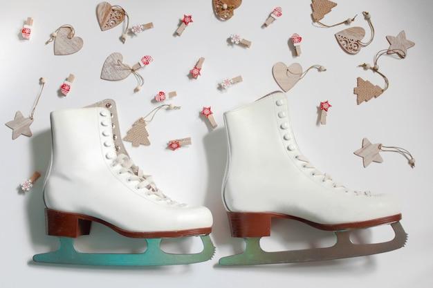 Two white figure skates on a white background around wooden christmas toys are lying. Premium Photo