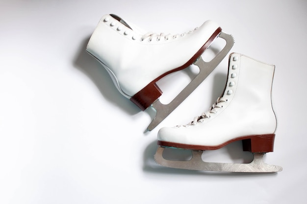 Two white figure skates on a white background there is a place for the inscription flatlay.