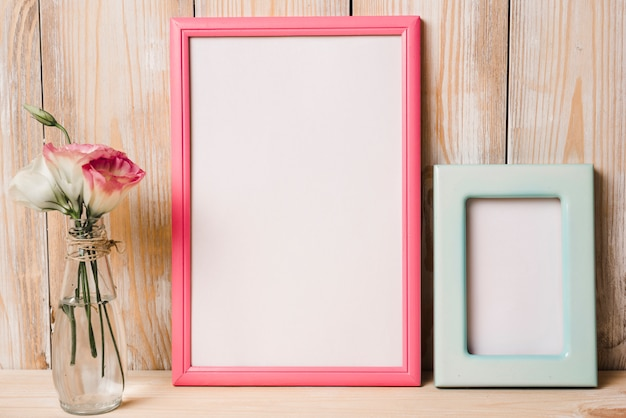 Two white frame with pink and blue border and flower vase against wooden background