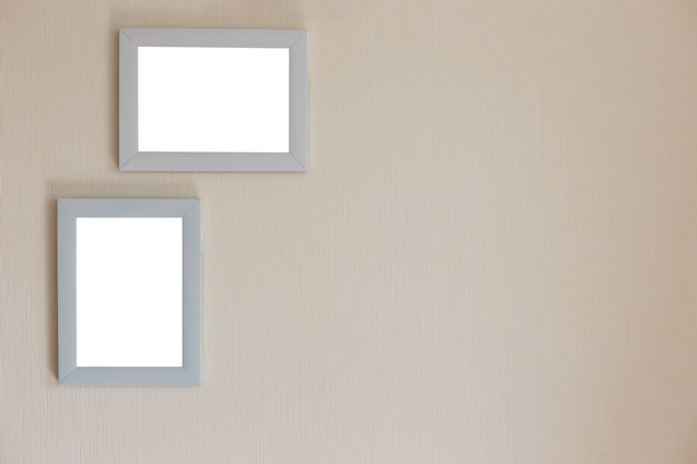 Two white frames on a beige wall