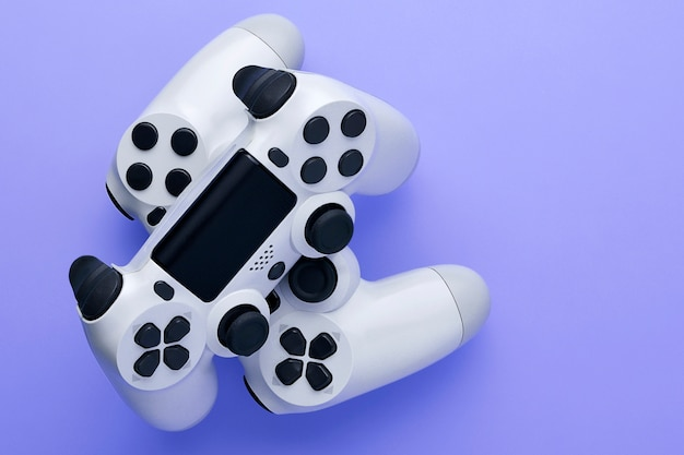 Two white gaming controller isolated on violet background with copy space.