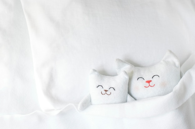 Two white handmade cats are sleeping on a white bed.