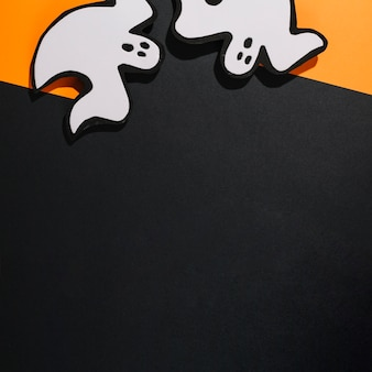 Two white handmade ghosts on orange paper