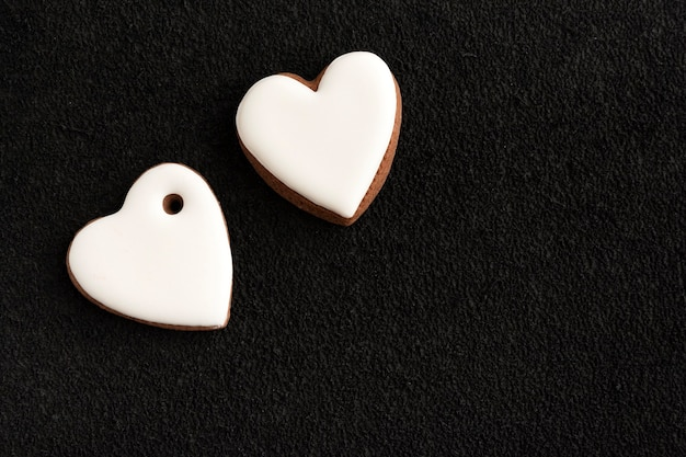Two white heart shaped gingerbreads on black background. copy space.