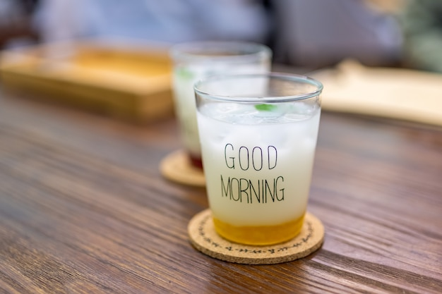 Two white iced drinks with the word good morning written on them are on the wooden table