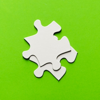 Two white jigsaw puzzle piece on bright green backdrop