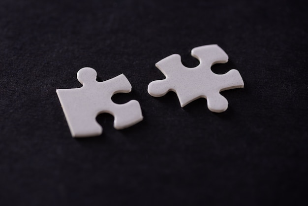 Две белые головоломки, изолированные на черном фоне.