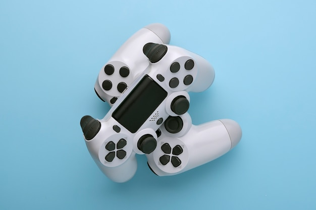 Two white joystick gamepad, game console on blue colourful trendy modern fashion pin-up background