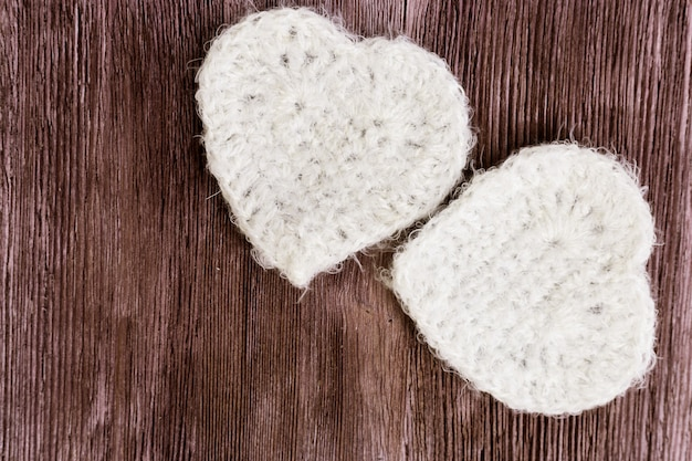 Two white knitted hearts on vintage wooden surface