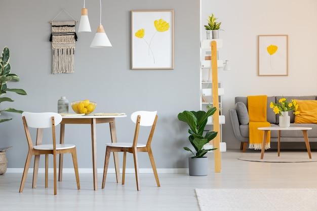 灰色のソファに黄色い毛布が付いたオープンスペースのアパートのインテリアの丸いダイニングテーブルの上にある2つの白いランプ。本物の写真