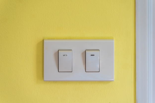 Two white lighting switchs on yellow concrete wall