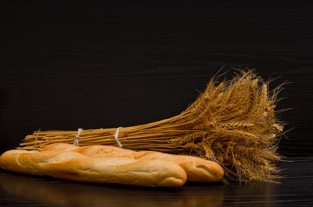 Two white loaf and a sheaf on a black background, with space for text