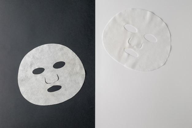 Две белые маски на черно-белом фоне. маска для ухода за лицом и изменения внешности.