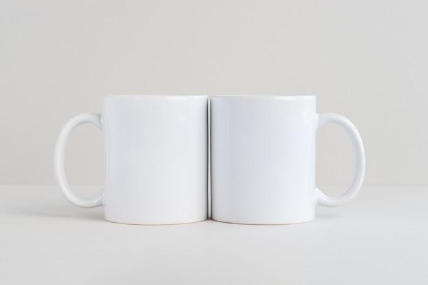 Две белые кружки на светло-сером фоне макета