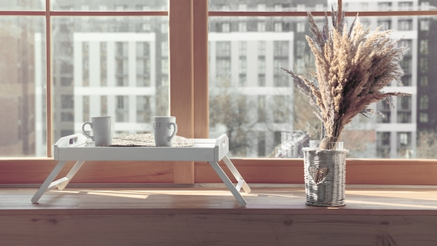 Two white mugs on serving table with flowers vase on window sill