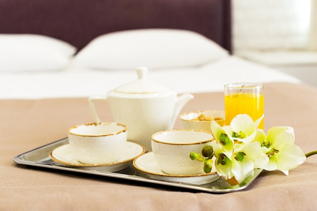 Two white mugs on a tray white bed, breakfast concept