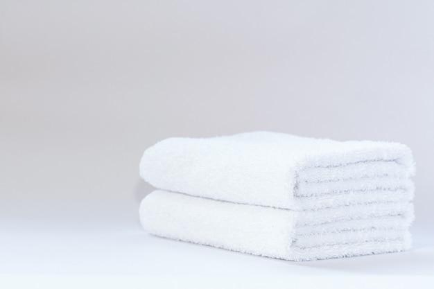 Два белых аккуратно сложенных махровых полотенца