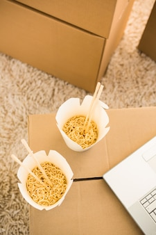 Two white noodles boxes put on a box