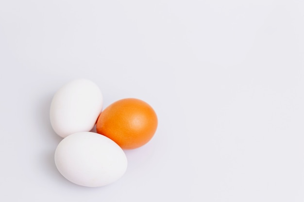 Two white and one brown egg on a white background. healthy diet food. space for text.