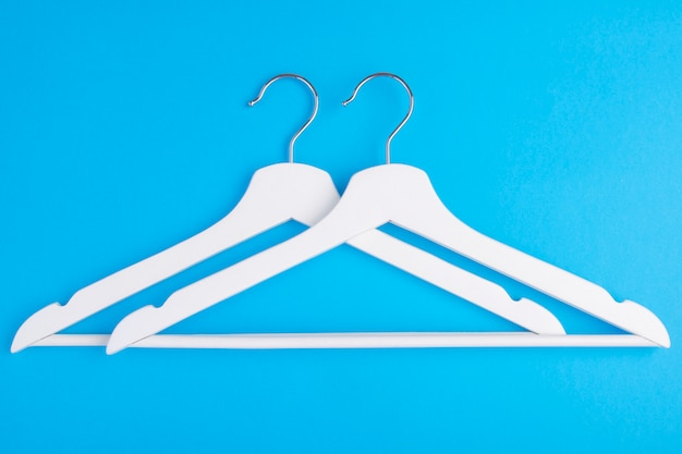 Two white overlapping wooden coat hangers on fa blue.