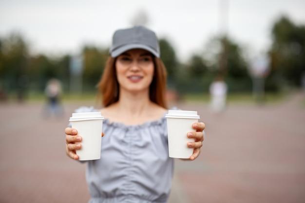 女性の手にコーヒーと2つの白い紙コップ。街でコーヒーを飲む時間。行くコーヒー。瞬間を楽しんで、休憩してください。使い捨ての紙コップのクローズアップ。美味しい温かい飲み物。テキスト用の空白スペース、