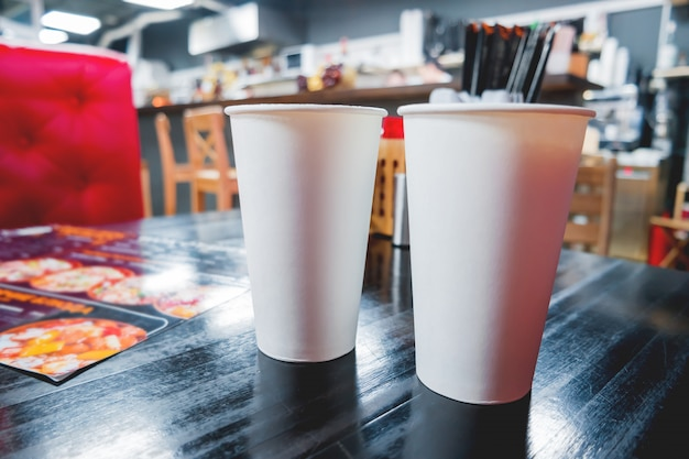 Two white paper glasses with coffee on cafe table