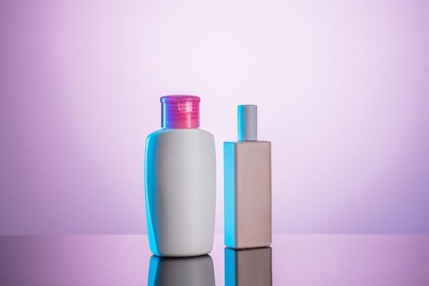 Две белые пластиковые бутылки на бело-розовом фоне. гигиеническое понятие.