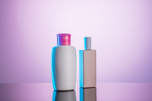 Two white plastic bottles on white-pink background. hygienic concept.