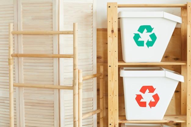 ワークショップの木製テーブルに2つの白いプラスチック製のゴミ箱