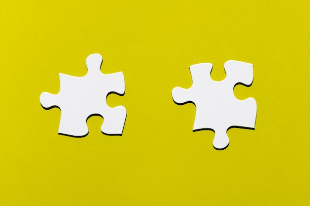 Two white puzzle piece on yellow backdrop