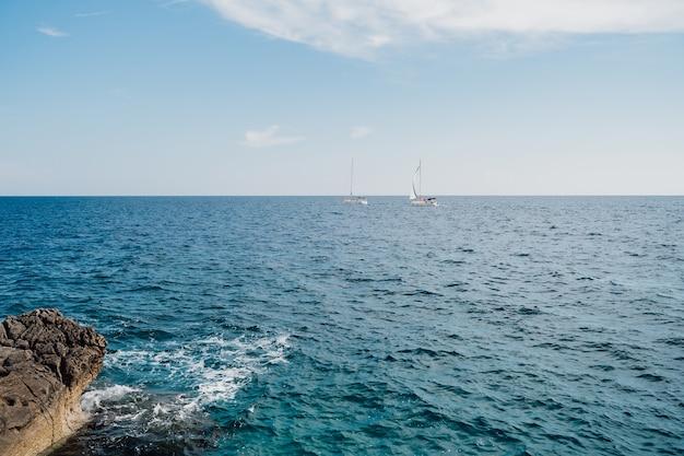 岩の多い海岸からの晴れた明るい日の景色を眺めながら、2隻の白い帆船が外洋を航行しています