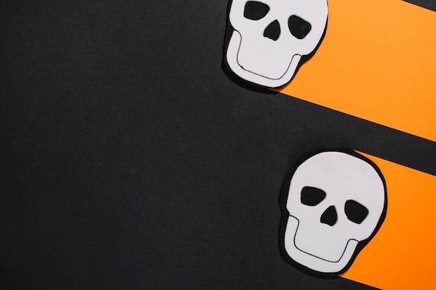 オレンジ色の紙に2つの白い頭蓋骨