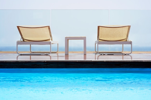 Two white summer sun loungers on a wooden floor