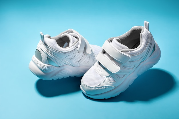 Two white teen hovering in the air running shoes isolated on a blue background with hard shadows