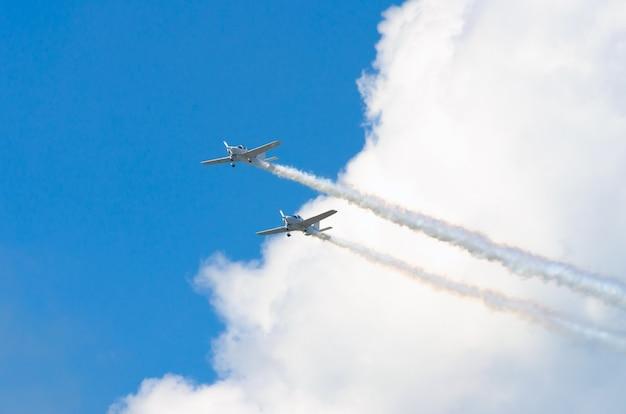 青い空を背景に白い煙の痕跡がある2つの白いターボプロップ飛行機。