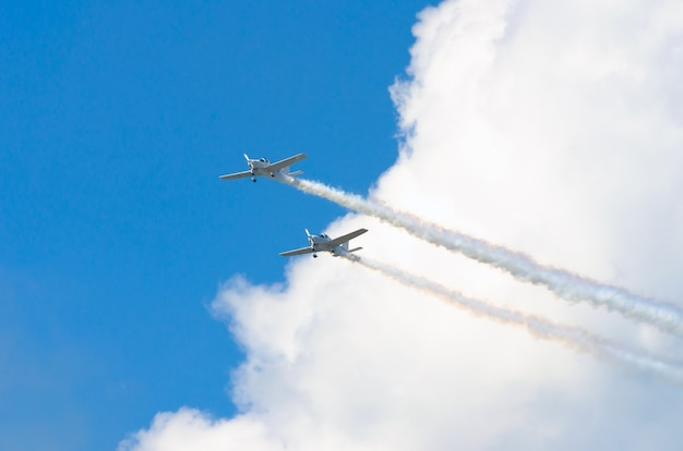 Two white turboprop airplane with a trace of white smoke against a blue sky.