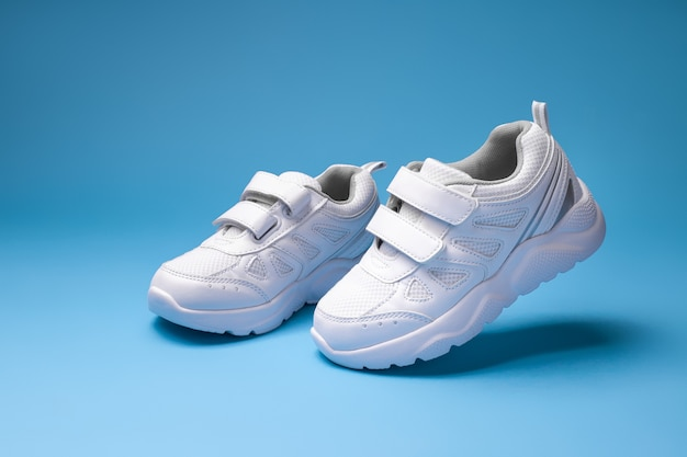 Two white unisex running shoes simulate walking and flying in the air isolated on a blue background