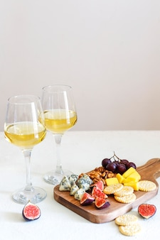 Two white wine glass and cheese board with nuts