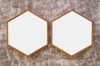 Two white wooden hexagon frame on wallpaper