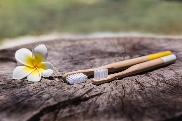 Two white and yellow eco friendly bamboo wooden toothbrushes on wooden Premium Photo
