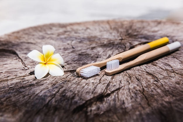 Two white and yellow eco friendly bamboo wooden toothbrushes on wooden